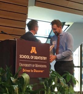 A graduating student receives the Mentor Award at Minnesota's School of Dentistry Senior Awards Night