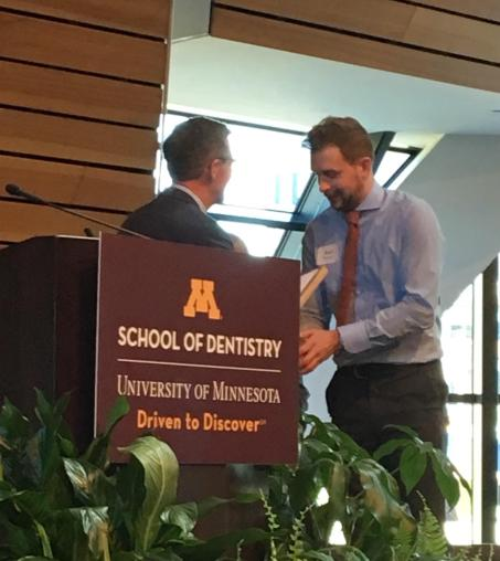 A graduating student receives the Mentor Award at Minnesota's School of Dentistry Senior Awards Night